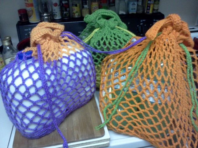 Reusable mesh market bags, cinched tight with drawstrings.